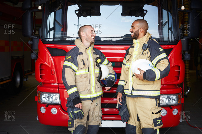 Happy firefighters talking while standing in front of fire engine at fire station