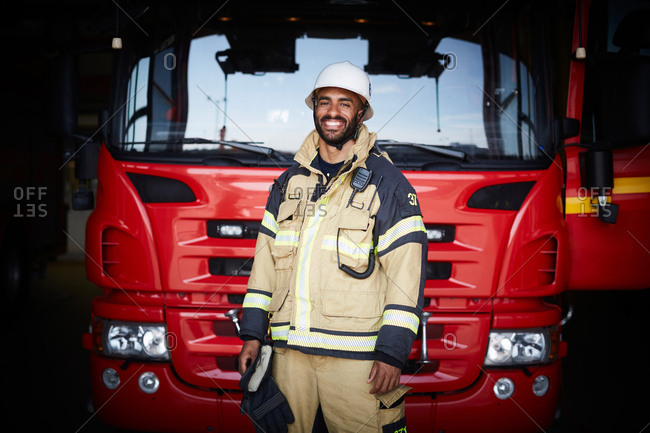 Portrait of smiling firefighter in uniform standing against fire engine at fire station