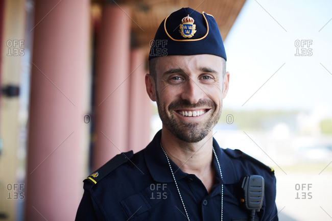 Portrait of smiling policeman standing outside police station