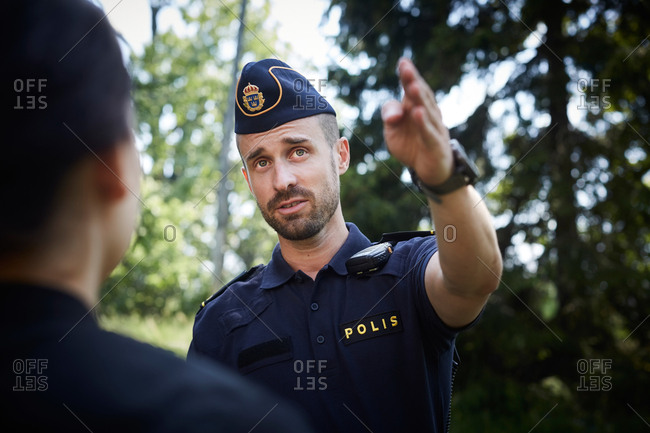 Male police officer gesturing while directing woman outdoors