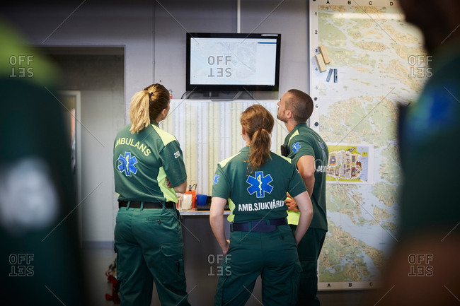 Paramedics discussing while looking at screen in hospital