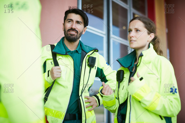 Male and female paramedics discussing while standing outside hospital