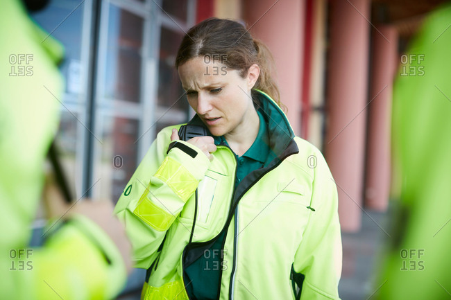 Female paramedic talking on walkie-talkie with coworker outside hospital