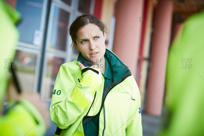 Female paramedic looking away while talking on walkie-talkie outside hospital