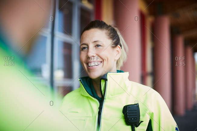 Smiling female paramedic looking away standing outside hospital