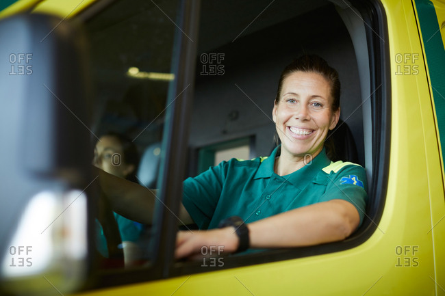 Portrait of smiling mature female paramedic driving ambulance in parking lot