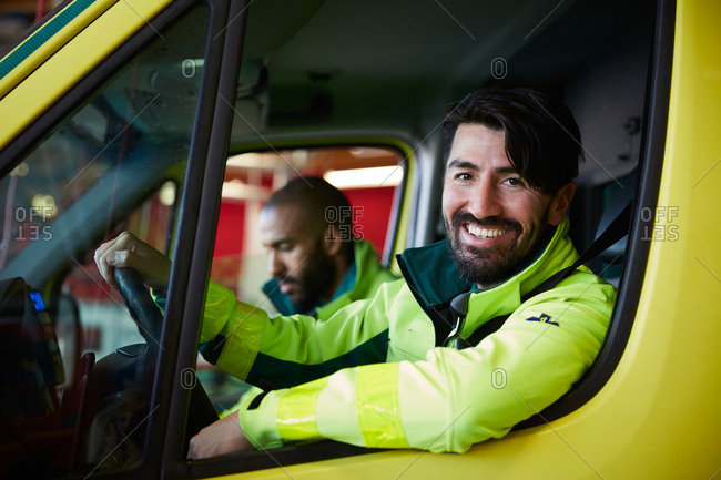 Portrait of smiling male paramedic with coworker driving ambulance in parking lot