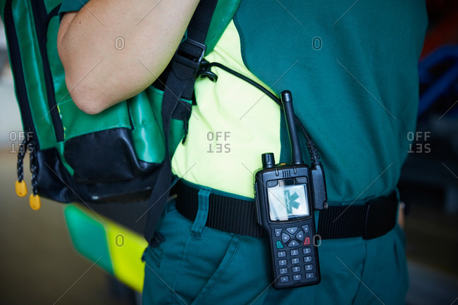 Midsection of female paramedic with walkie-talkie on belt in parking lot
