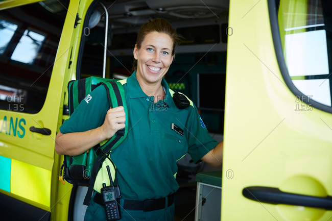 Portrait of smiling paramedic standing outside ambulance in parking lot