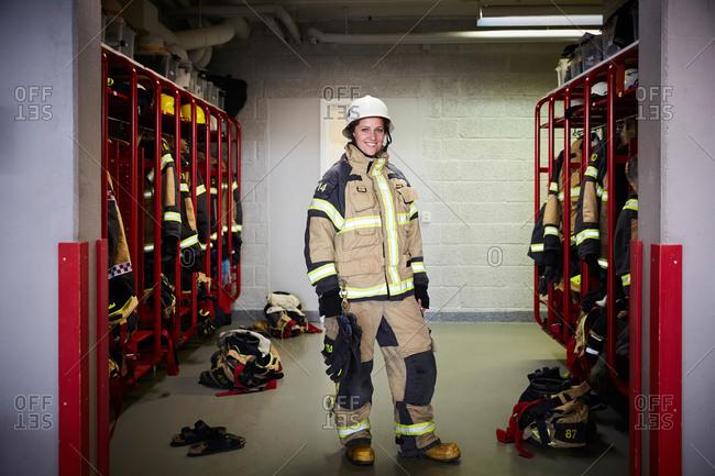 Full length portrait of smiling female firefighter standing in locker room at fire station