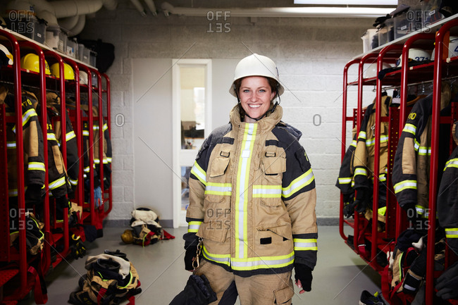 Portrait of smiling female firefighter standing in locker room at fire station