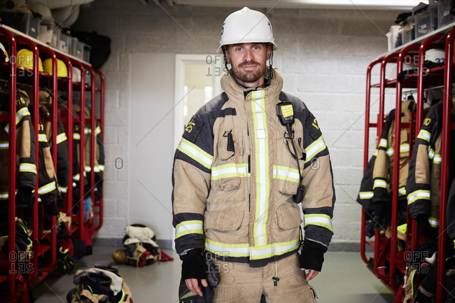 Portrait of confident male firefighter wearing protective uniform standing in locker room at fire station