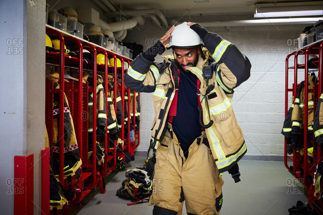Mid adult firefighter wearing work helmet in locker room at fire station