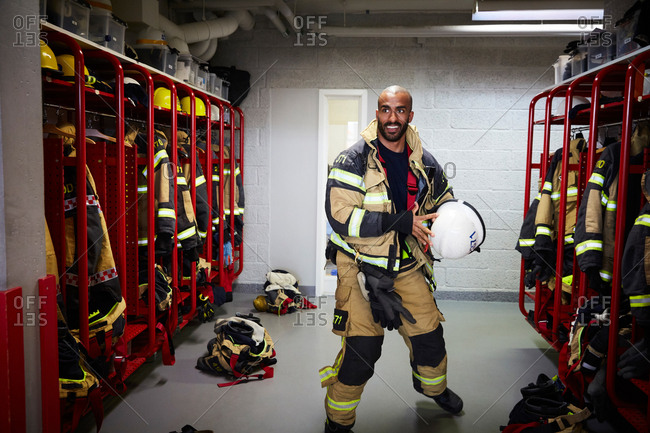 Male firefighter holding work helmet in locker room at fire station
