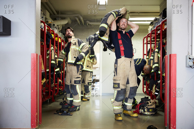 Firefighters wearing protective workwear in locker room while looking up at fire station