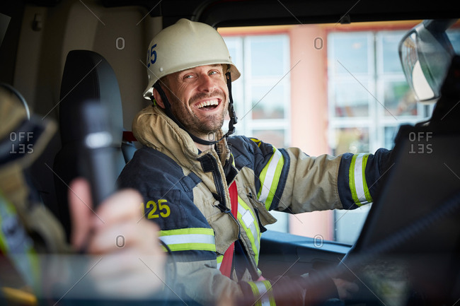 Smiling firefighter looking at coworker while sitting in fire engine