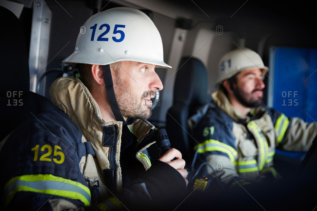 Firefighter talking on microphone while sitting with coworker in fire engine