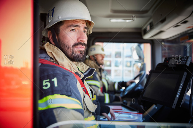 Firefighter looking through window while sitting in fire truck