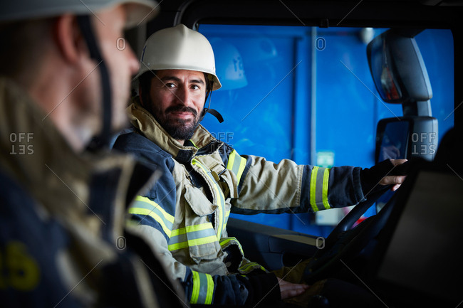 Firefighter looking at coworker while sitting in fire truck