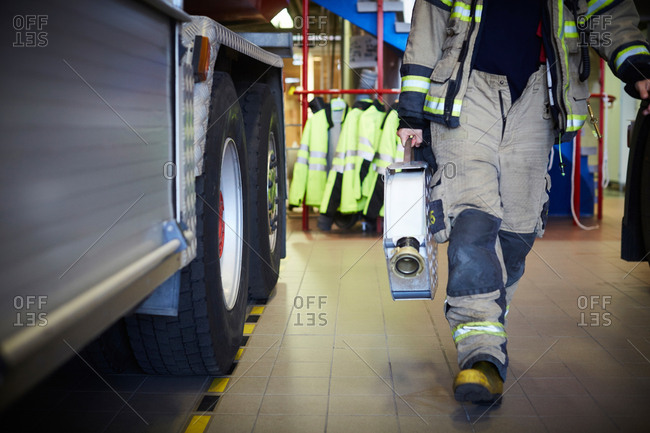 Low section of firefighter holding fire hose while walking at fire station