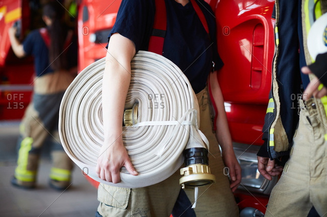Midsection of female firefighter holding rolled up fire hose while standing with coworker at fire station