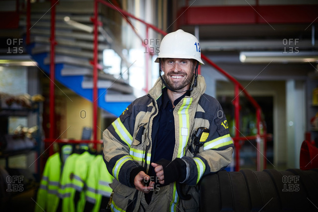Portrait of smiling firefighter wearing protective suit at fire station
