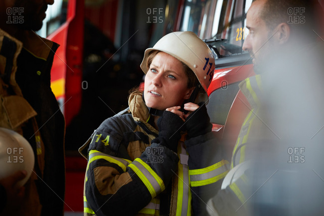Female firefighter wearing helmet while talking with other coworkers in fire station