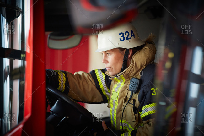 Female firefighter wearing helmet sitting in fire truck at fire station