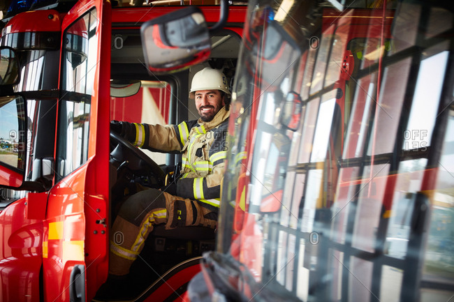 Portrait of smiling male firefighter sitting in fire truck at fire station