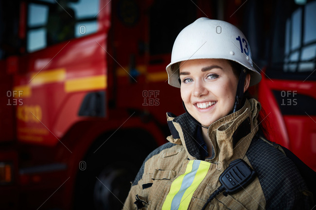 Portrait of smiling female firefighter in helmet at fire station
