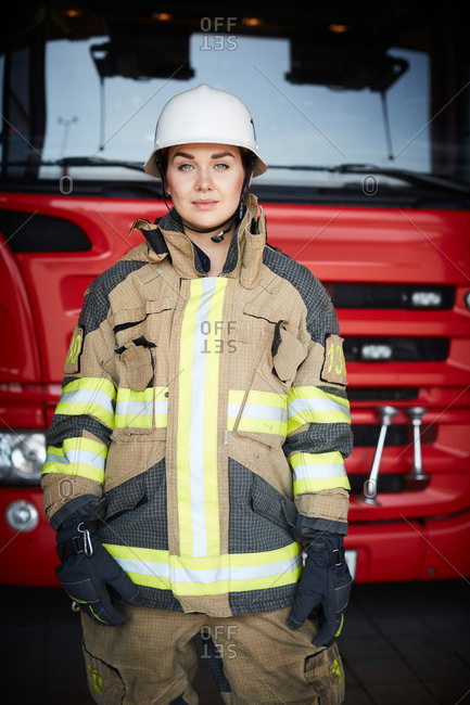 Portrait of confident firefighter standing in front of fire engine at fire station