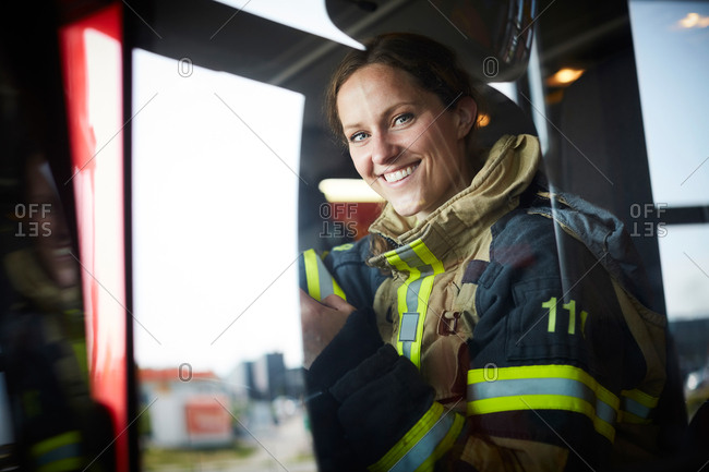 Portrait of smiling female firefighter sitting in fire engine