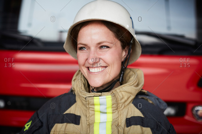 Smiling female firefighter wearing helmet looking away in fire station