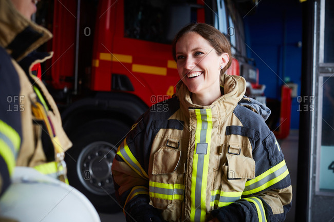 Smiling female firefighter looking at coworker while communicating in fire station