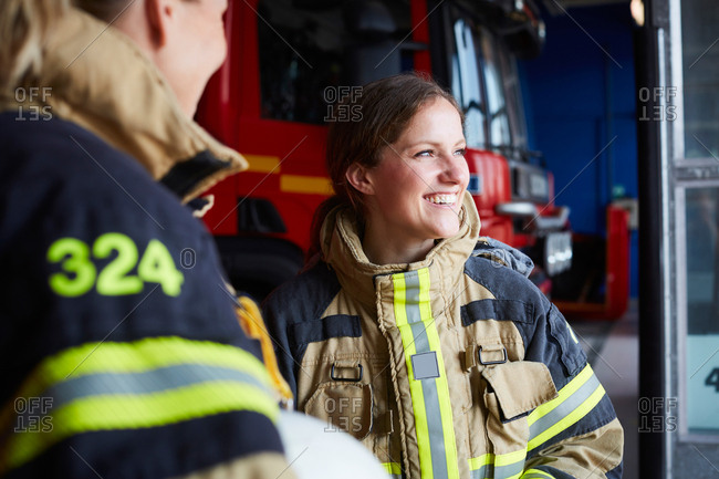 Smiling female firefighter standing with coworker in fire station