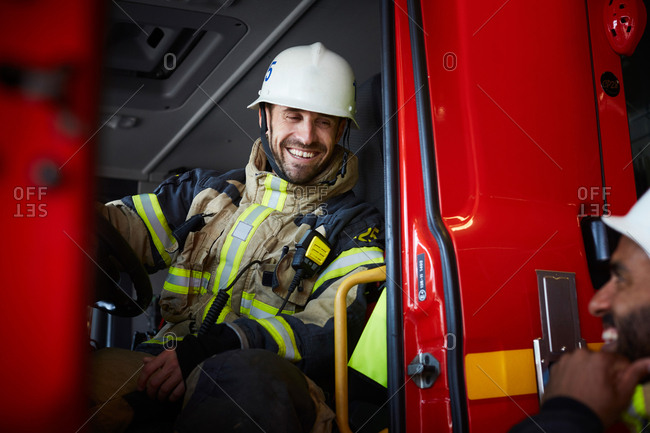 Smiling firefighter sitting in fire engine while talking to coworker