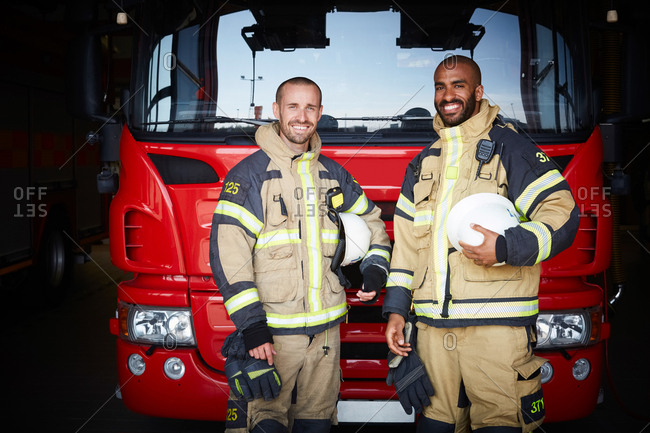 Portrait of coworkers standing in front of fire engine at fire station