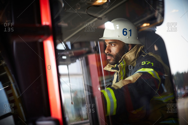 Confident firefighter looking away while sitting in fire engine