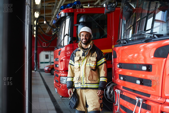 Portrait of smiling firefighter standing by fire engine at fire station