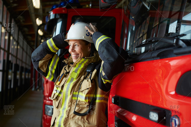 Smiling female firefighter wearing helmet while standing by fire engine at fire station