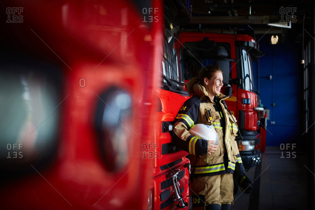 Smiling female firefighter standing by fire engine at fire station