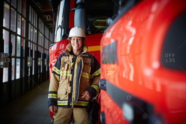 Portrait of smiling female firefighter standing by fire truck at fire station