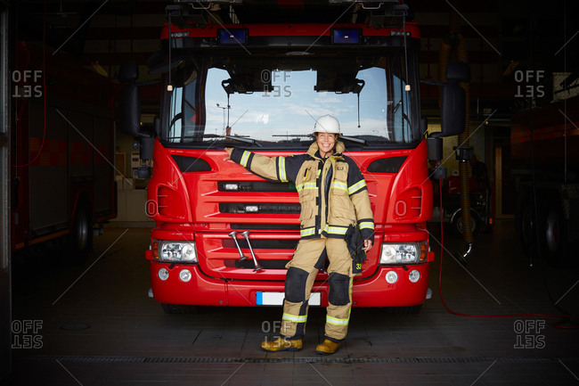 Full length portrait of smiling female firefighter standing in front of fire engine at fire station