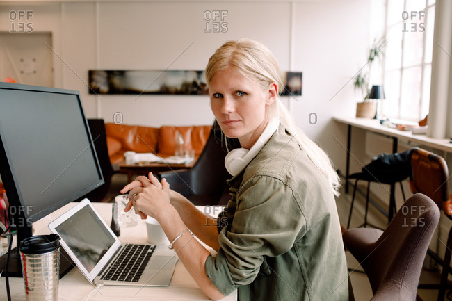 Portrait of female entrepreneur sitting on chair in workplace