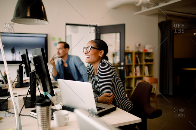 Smiling female colleague sitting by coworker at desk in workplace