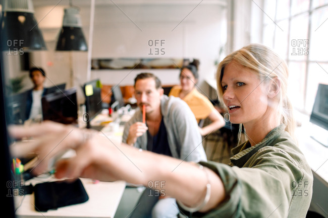 Female entrepreneur explaining business strategy to coworkers in office meeting