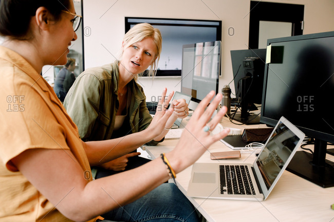 Female business professionals discussing over laptop while sitting at desk in office
