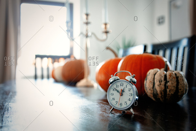 vintage alarm clock with pumpkins on a table