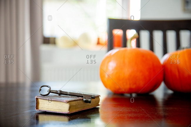 vintage book and key with pumpkins on a table