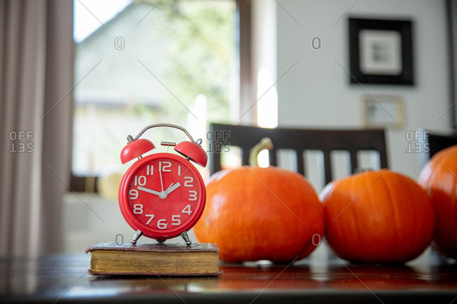 vintage book and alarm clock with pumpkins on a table